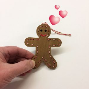 Handmade wooden gingerbread man ornament with hand.