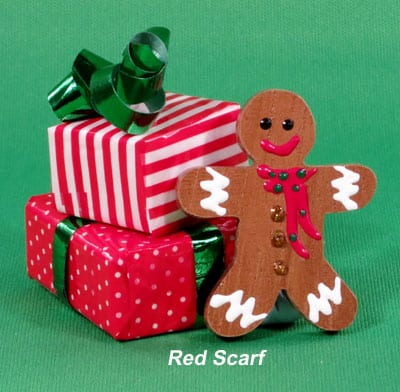 Wooden gingerbread man brooch with red scarf.