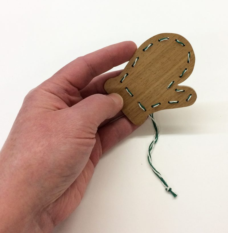 Handmade gingerbread mitten ornament with hand.
