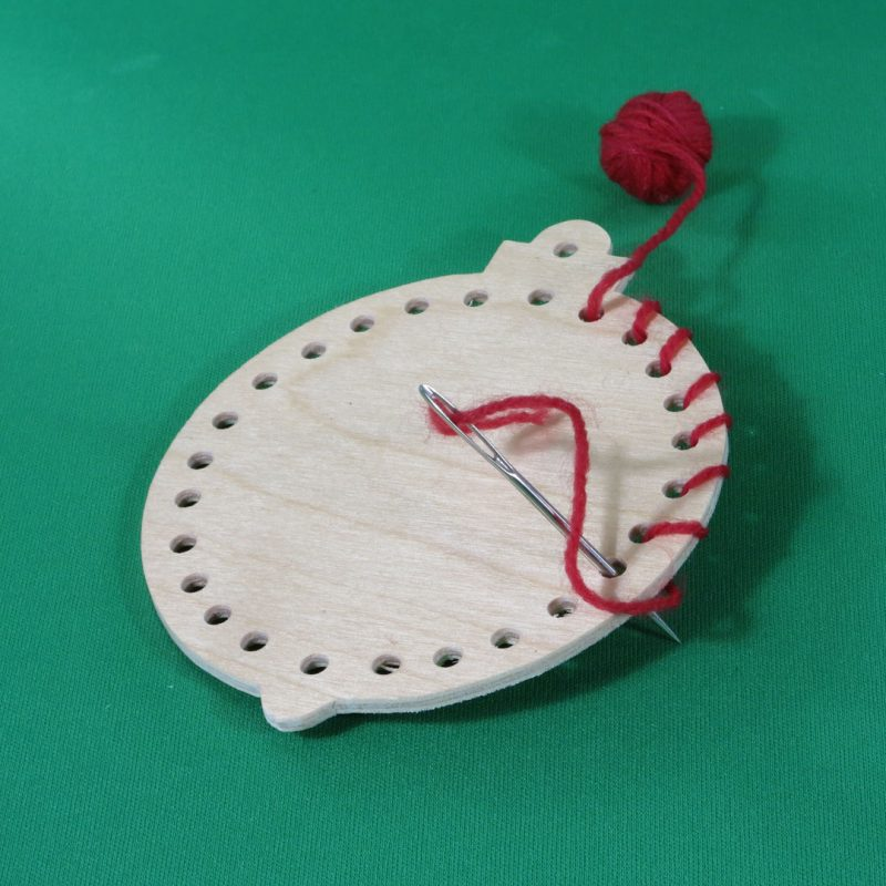 Handmade wooden round-lacing-ornament-with-yarn.