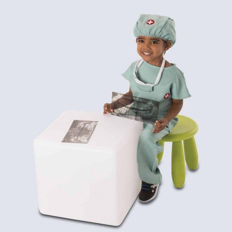Boy dressed as dentist holding Roylco dental xrays.