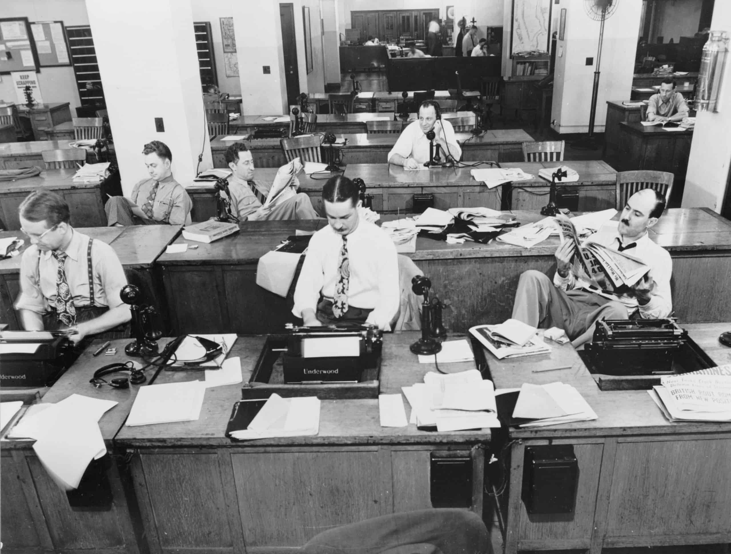 Black and white image of newsroom with journalists at desks.