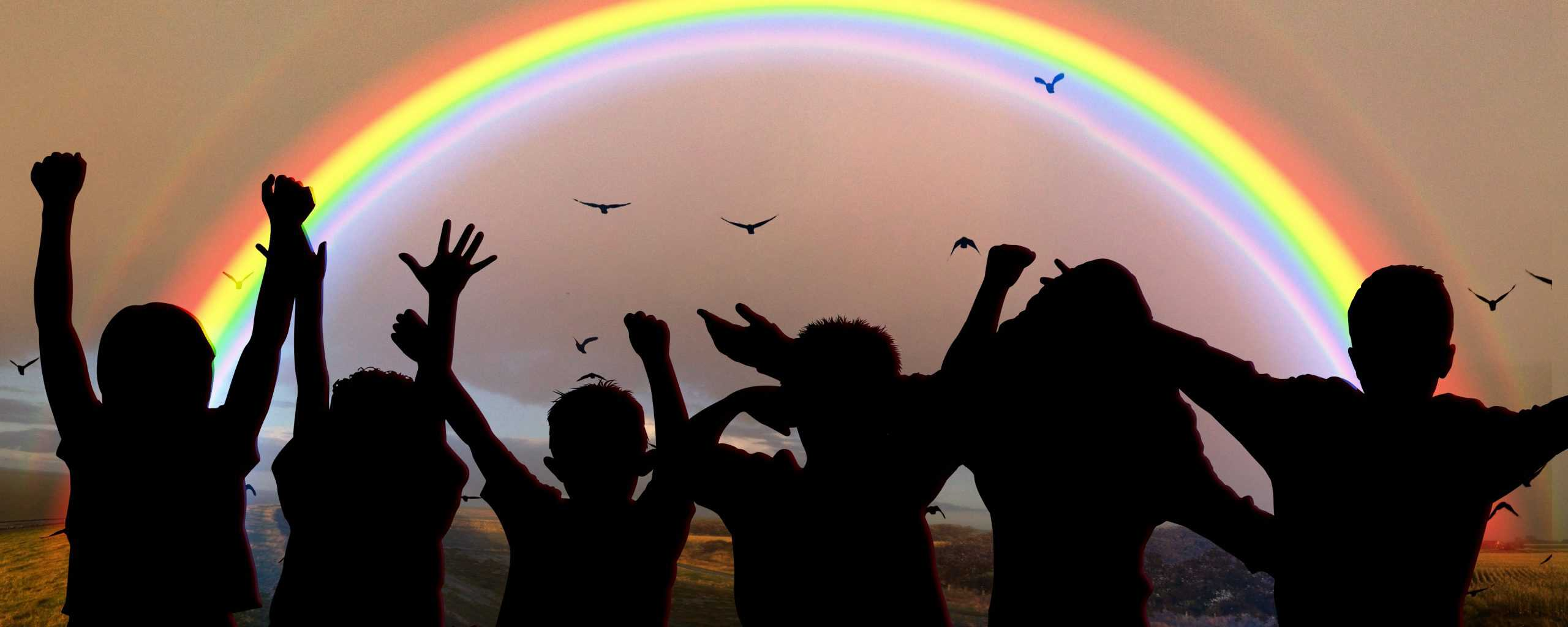 Silhouettes of children in front of a rainbow.