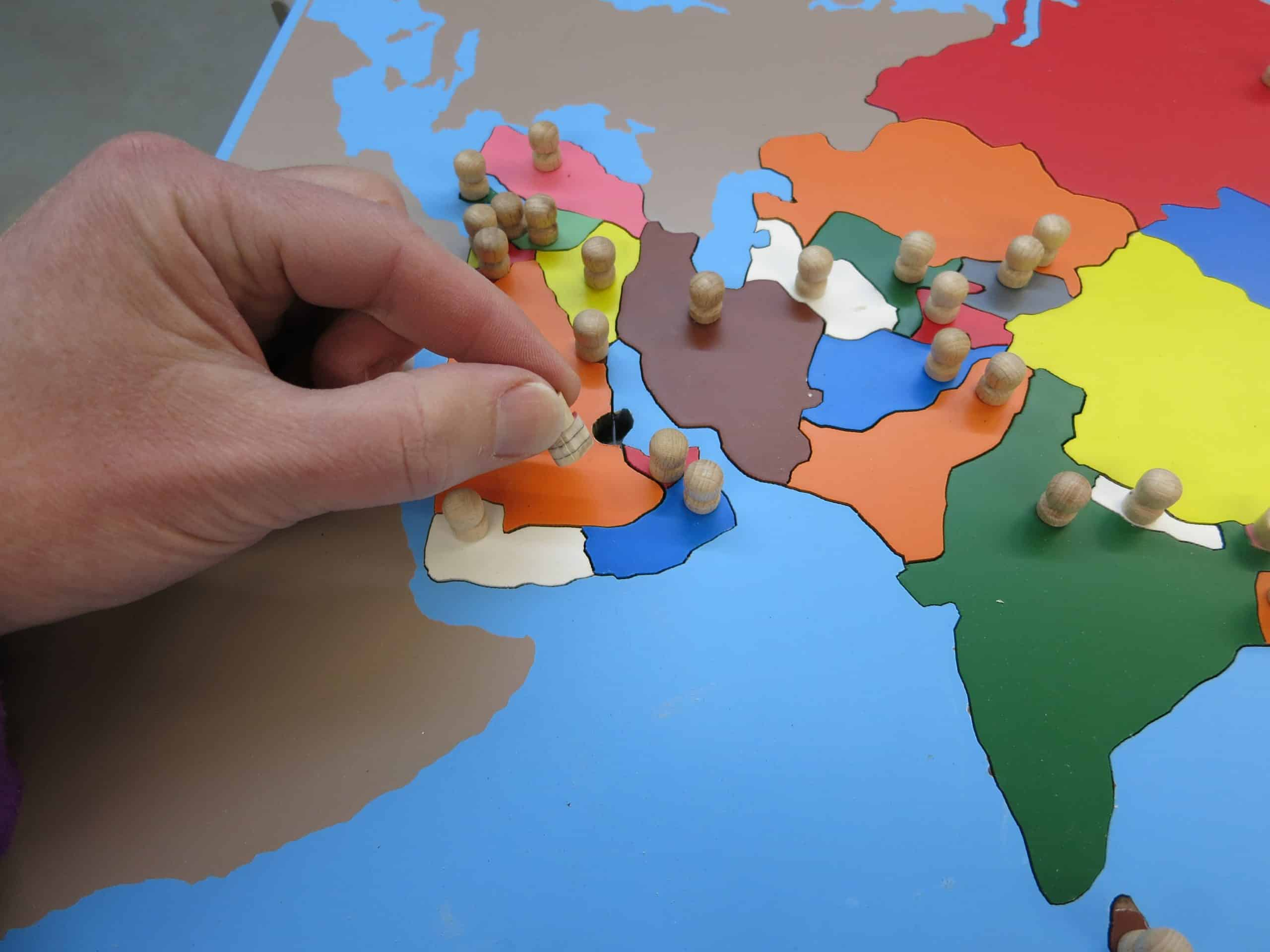 Montessori puzzle map showing the pincer grip of picking up a piece.